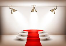 Showroom with red carpet leading to a podium and three lights. Royalty Free Stock Images