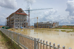 It shows construction cranes and unfinished house on the skylin Royalty Free Stock Image