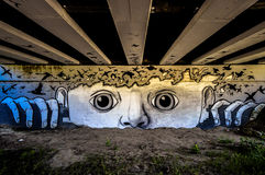 It shows the fly of a flock inside the mind of a person, couriously watching who is passing under the bridge. Graffiti under italian park in Scandiano. It shows royalty free stock images