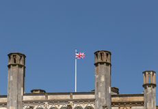 Shows a Union Jack flag flying on top of a castle roof. Shot on a bright sunny summers day, Union Jack fluttering stock photography