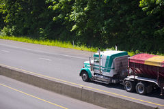 Showy Semi truck classic rig and colored tilt trailer Royalty Free Stock Photo