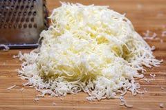 Shredded сыр моццареллы на разделочной доске стоковые фото