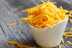 Shredded cheddar cheese in white cup  close up view Stock Photos