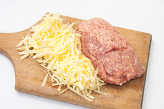 Shredded cheese and minced meat on a kitchen wooden board Stock Image