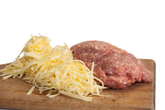 Shredded cheese and minced meat on a kitchen wooden board Stock Images