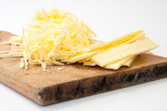 Shredded cheese on wooden kitchen board Royalty Free Stock Photos