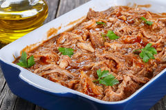 Shredded chicken meat tossed in sauce. Delicious Shredded chicken meat tossed in barbecue sauce, loaded with smoky chipotle flavours in baking dish, on old Royalty Free Stock Photo