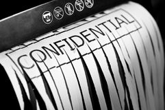 Shredded confidential document. A sheet of partially shredded paper still in the shredding machine with the word confidential Stock Image