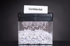 Shredded destroying confidential document. Over black background Stock Photography