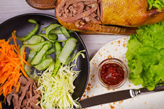 Shredded duck, carrot, cabbage, cucumber, salad, tomato sauce and flat bread. Ingredients for rolls, wraps, burritos. View From Ab Royalty Free Stock Photos