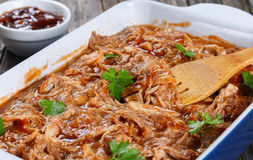 Shredded meat tossed in barbecue sauce. Delicious Shredded meat tossed in barbecue sauce in dish with wooden fork spatula, on old wooden table with sauce on Stock Images