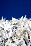 Shredded Paper 1. Vertical photo of shredded paper on a blue background with room for text Royalty Free Stock Photos