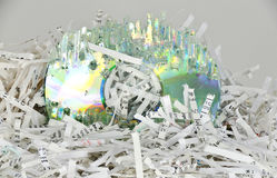 Shredded papers and a destroyed data disc Royalty Free Stock Photos