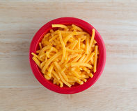 Shredded sharp cheddar cheese in red bowl Royalty Free Stock Images