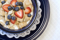 Shredded wheat cereal. Bite size shredded wheat biscuit cereal with sliced strawberries, whole blueberries and milk in blue bowl royalty free stock photography