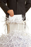 Shredder overflow. Business man shredding confidential documents at overflowing shredder Stock Images