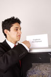 Shredding an employee development plan. Young male shredding his own Employee Development plan royalty free stock image