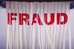 Shredding fraud. A white piece of paper with fraud written in red writing going through the shredder Royalty Free Stock Photos