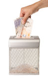 Shredding Money. Hand feeding money into a document shredder. Wasting money. Isolated on white with clipping path Stock Image