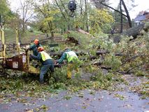 Shredding Tree Limbs. Photo of utility crew cleaning up downed tree and limbs on 10/30/12 on newark street in northwest washington dc.  The hurricane did not Stock Image