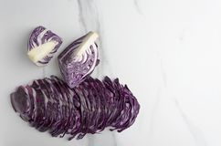 Shreded red cabbage and halves of it o n white marble table in the kitchen,top view stock photography