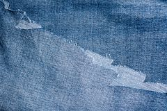 Shreds of denim fabric, unevenly cut jeans Stock Image