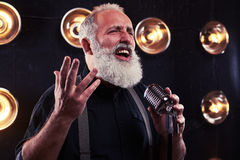 A shrewd look of emotional gray bearded man singing in a silver. Studio portrait of shrewd look of emotional gray bearded man singing in a silver vintage stock image
