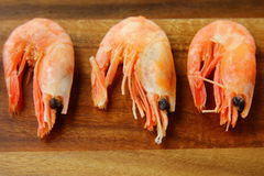 Shrimp. Many red shrimp are ready on a wooden board stock photo