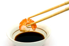 Shrimp. In chopsticks and soy sauce Royalty Free Stock Images
