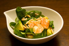 Shrimp avocado salad. A shrimp and avocado salad appetizer in a bowl on a wooden table under warm light Stock Photo