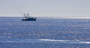 Shrimp Boat on Blue Seas. A shrimp boat off the coast in the morning Royalty Free Stock Image