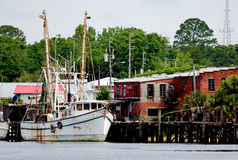 Shrimp boat docked at a wooden pier stock photography