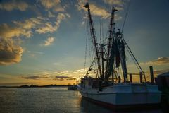 A Shrimp Boat Tied to a Pier at Sunset royalty free stock photography