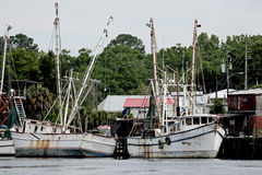 Shrimp boats docked at a wooden pier Stock Images