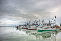 Shrimp Boats in a Row. Row of shrimp boats docked in Fulton, Texas marina as bad weather approaches Royalty Free Stock Photo