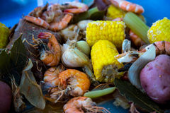 Shrimp Boil. Boiled shrimp and vegatables on tray with spice bag royalty free stock images