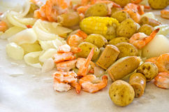 Shrimp boil. Dinner with shrimp, onions, sausage, and potatoes on white butcher paper stock photography