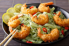 Shrimp in breadcrumbs with green pasta, chili pepper and sesame stock images