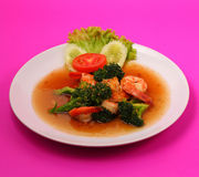 Shrimp broccolli stir fry. Shrimp and broccoli stir fry in sauce with a pink background Royalty Free Stock Images