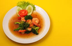 Shrimp broccolli stir fry. Shrimp and broccoli stir fry in sauce with a yellow background Royalty Free Stock Photography