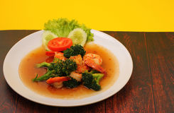 Shrimp broccolli stir fry. Shrimp and broccoli stir fry in sauce with a yellow background on a wood table Stock Images