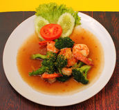 Shrimp broccolli stir fry. Shrimp and broccoli stir fry in sauce with a yellow background on a wood table Stock Image