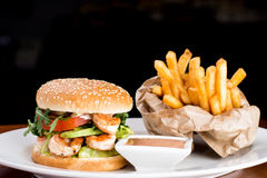 Shrimp Burger with fries and souce. Juicy shrimp burger with fries and souce on white dish and dark background stock photo