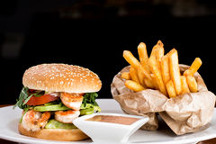 Shrimp Burger with fries and souce. Juicy shrimp burger with fries and souce on white dish and dark background stock images