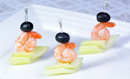 Shrimp and Celery Appetizers. Small appetizers made of boiled shrimp, celery and black olives royalty free stock photography