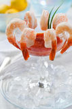 Shrimp Cocktail. A traditional shrimp cocktail with seafood sauce, lemons, and chives on ice Stock Images