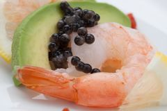 Shrimp Cocktail with Black Caviar. Close up of delicious appetizer shrimp cocktail with black caviar. Garnished with avocado, lemon, and horseradish cocktail Royalty Free Stock Image