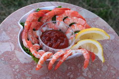 Shrimp cocktail served outdoors. Bowl of chilled shrimp cocktail with lemon wedges on served outdoors on a marble table Stock Image
