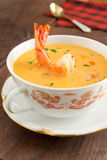 Shrimp cream soup in vintage red cream bowl, on antique walnut table. Royalty Free Stock Image