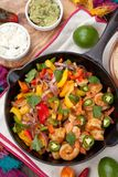 Shrimp Fajitas In Cast Iron Skillet. Shrimp fajitas with bell pepper, onion, and jalapeno in cast iron skillet ready to be served. Guacamole, salse, and Stock Image